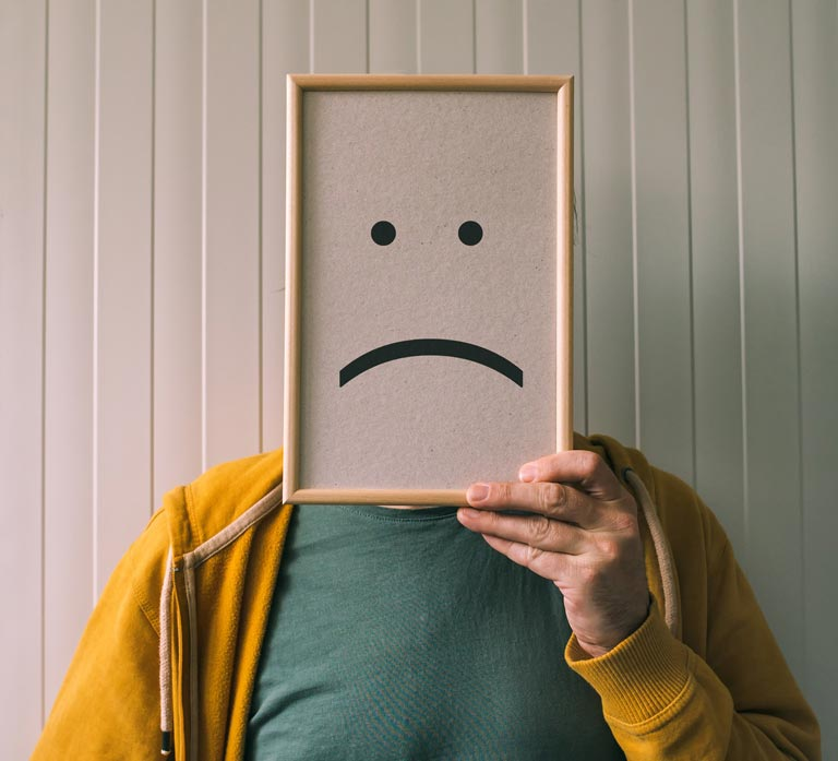 Man Holding Framed Frowning Face Symbol In Front Of His Head